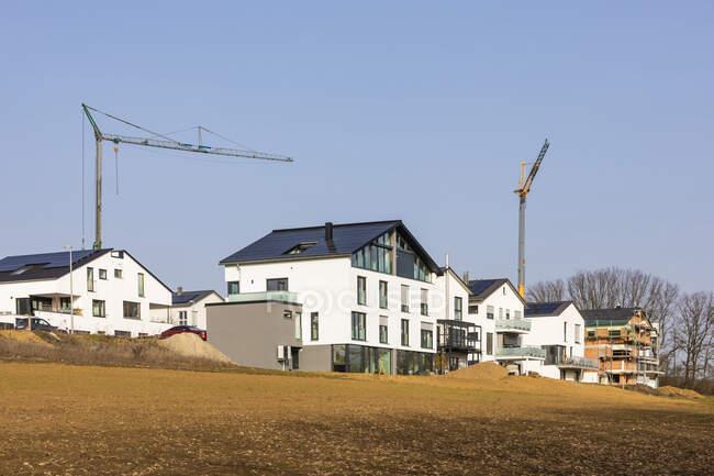Німеччина, Баден-Вуртемберг, Вайблінген, Сучасне енергоефективне передмістя з промисловими краном на задньому плані. — стокове фото