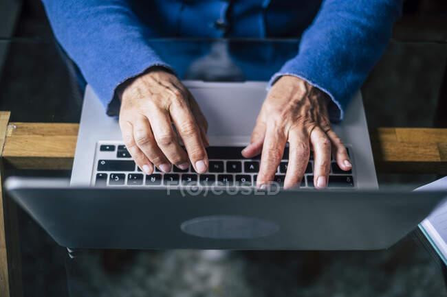 Женщина старший профессионал с помощью ноутбука в домашнем офисе — стоковое фото