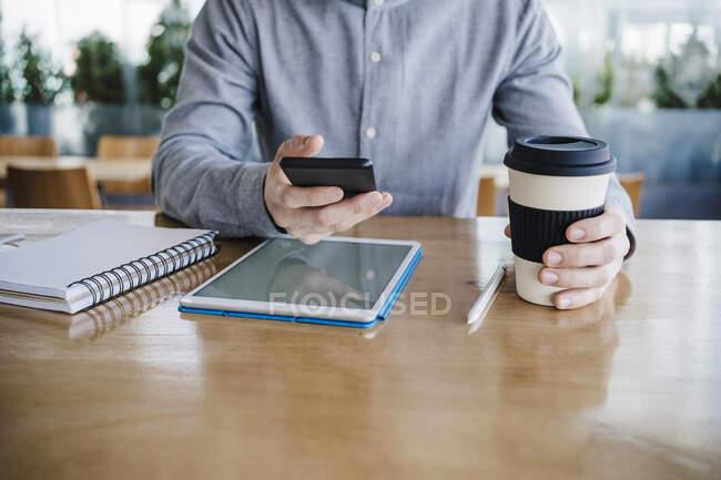 Homme d'affaires adulte moyen avec tasse de café réutilisable en utilisant le téléphone intelligent sur le bureau au bureau — Photo de stock