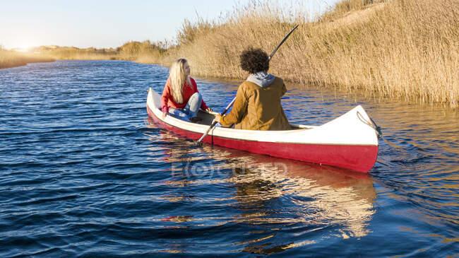 Fidanzato in canoa con fidanzata sul fiume durante il tramonto — Foto stock