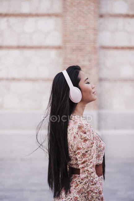 Mujer con el pelo largo usando auriculares mientras está de pie cerca de la pared - foto de stock
