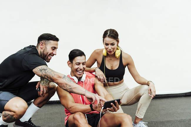 Веселих друзів, які дивляться на мобільний телефон, пригортаючись у спортзалі. — стокове фото