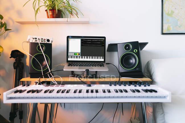 Электропианино и ноутбук в студии звукозаписи — стоковое фото