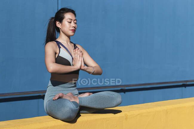 Молодая женщина с скрепленными руками, сидя скрещенными ногами, медитируя у голубой стены — стоковое фото
