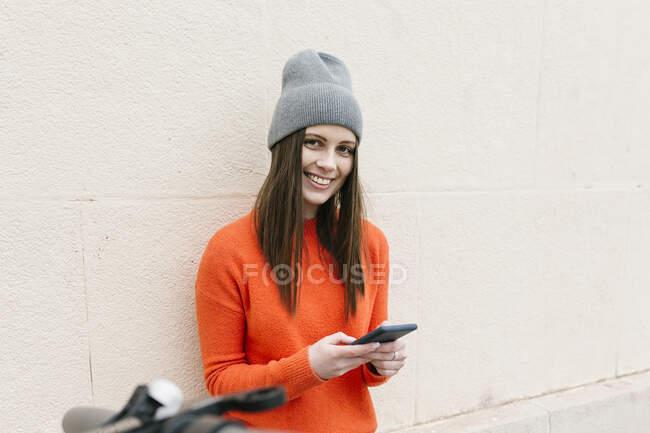 Mulher bonita em roupas quentes segurando telefone inteligente contra a parede — Fotografia de Stock