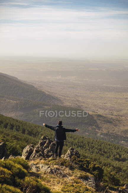 Turista masculino com braços estendidos em pé sobre a rocha durante as férias em Somosierra, Madrid, Espanha — Fotografia de Stock