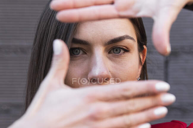 Woman with gray eyes making finger frame against wall — Stock Photo