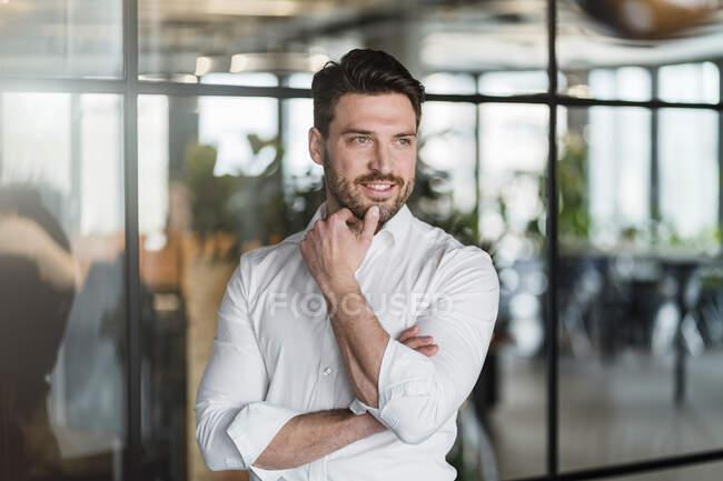 Sorridente uomo d'affari contemplativo in piedi sul posto di lavoro — Foto stock