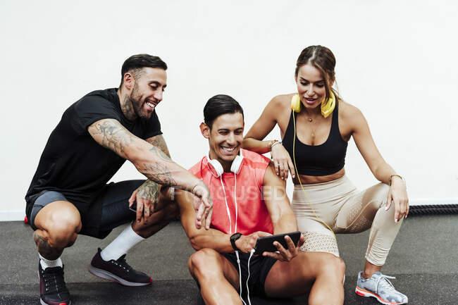 Посмішка спортсменів - чоловіків і жінок у спортзалі. — стокове фото