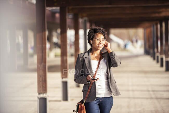 Jovem sorridente com celular ouvindo música através de fones de ouvido no dia ensolarado — Fotografia de Stock
