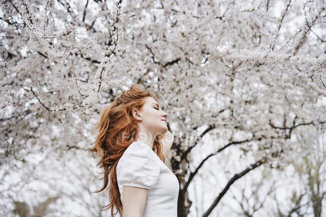 Mulher ruiva bonita com mão no cabelo no parque — Fotografia de Stock
