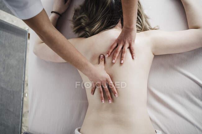 Fisioterapeuta femenina masajeando la espalda de una paciente sin camisa acostada en frente en el hospital - foto de stock