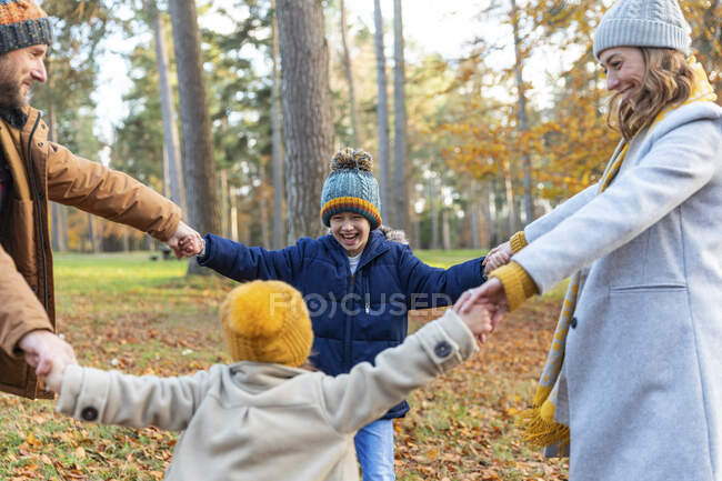 Happy family enjoying while playing in forest — Stock Photo