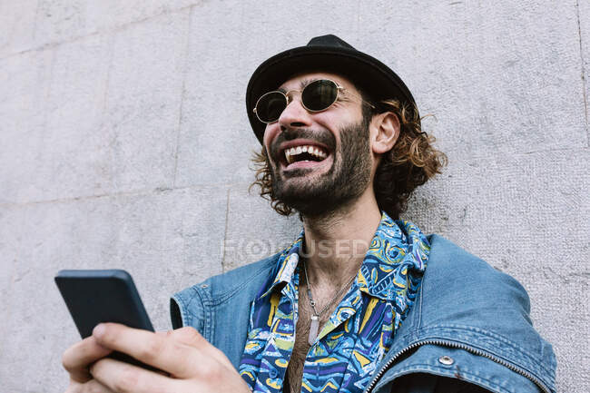 Rindo homem bonito com óculos de sol segurando telefone inteligente na frente da parede — Fotografia de Stock