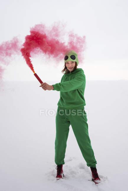 Bengala de angustia sostenida por la mujer en traje verde contra el cielo - foto de stock