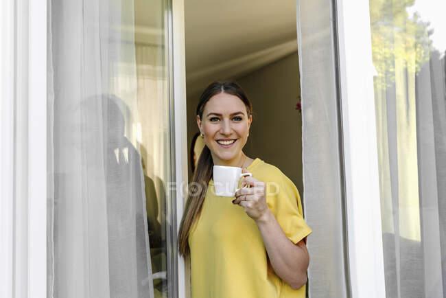 Bella donna sorridente prendere un caffè mentre in piedi alla finestra — Foto stock