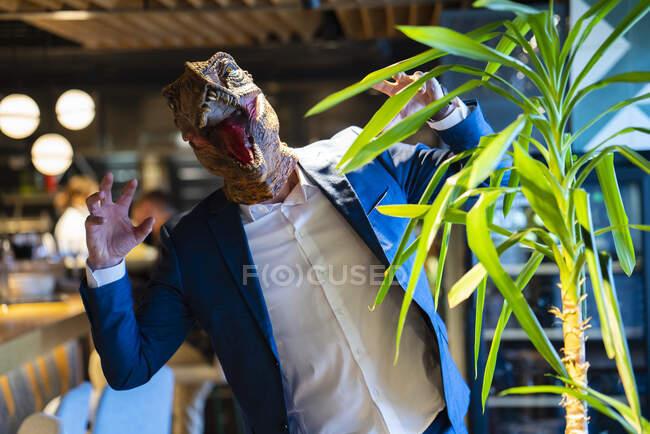Чоловік, який тримає жест, одягаючи маску динозавра в кафе. — стокове фото