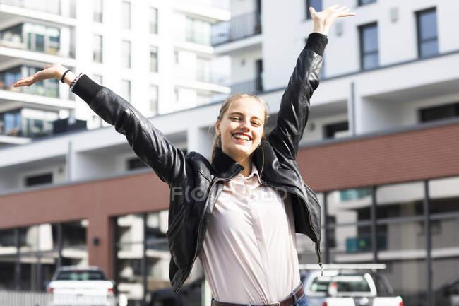 Ritratto di giovane bella bionda in piedi all'aperto e sorridente con le braccia alzate — Foto stock