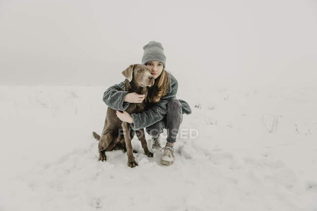 Ritratto di ragazza adolescente accovacciata nella neve e abbracciata Labrador Retriever — Foto stock