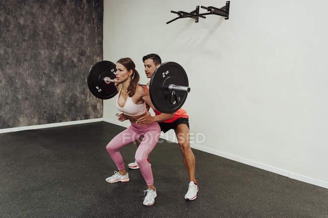 Mulher levantando barra durante o exercício com instrutor de fitness no health club — Fotografia de Stock
