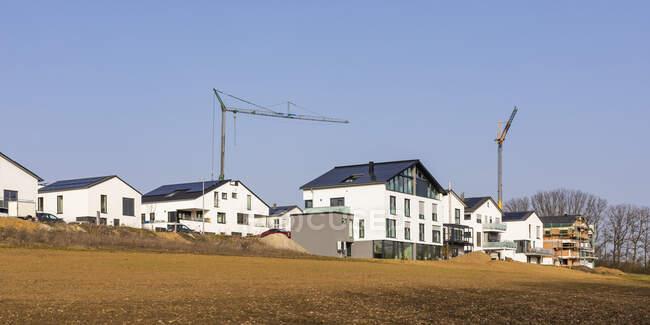 Німеччина, Баден-Вуртемберг, Вайблінген, панорама сучасного енергоефективного передмістя з промисловими краном на задньому плані. — стокове фото