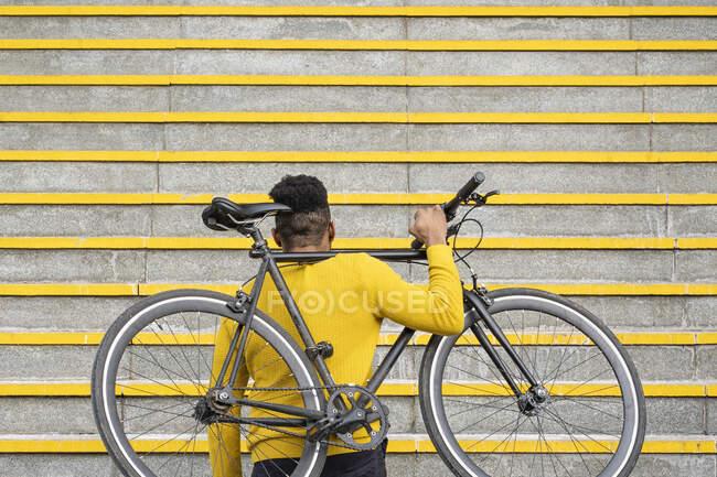 Чоловік, що носить велосипед на плечах на сходах. — стокове фото