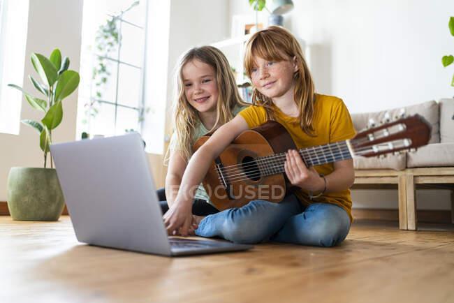 Tutorial de guitarra e-learning de chicas sonrientes a través de computadora portátil en la sala de estar en casa - foto de stock