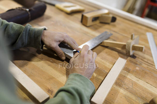 Male carpenter measuring wood material on table in workshop — Stock Photo