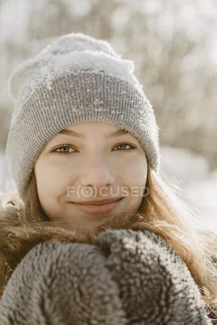 Портрет красивой девушки-подростка в вязаной шляпе, улыбающейся в камеру — стоковое фото