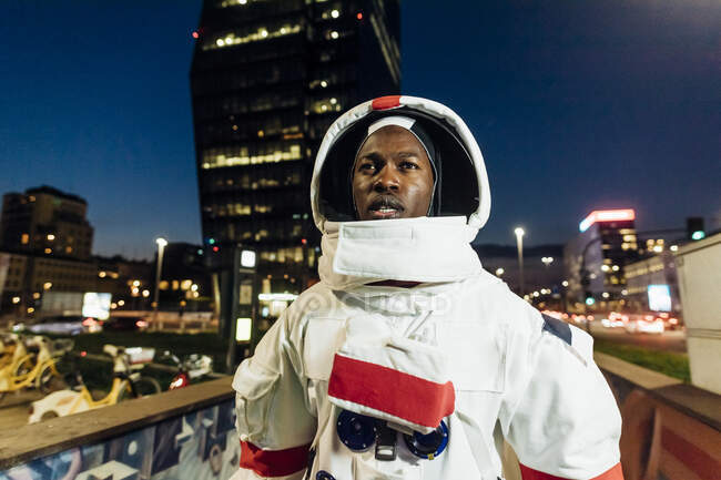 Male astronaut looking away while standing in city during night - foto de stock