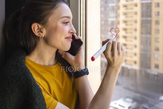 Mujer joven dibujando el corazón mientras habla en el teléfono móvil en casa - foto de stock
