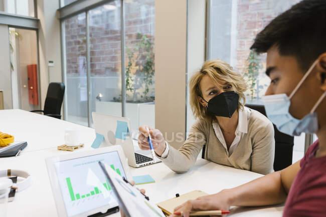 Profesional femenino explicando estrategia de negocio a compañero de trabajo masculino en escritorio en la oficina - foto de stock