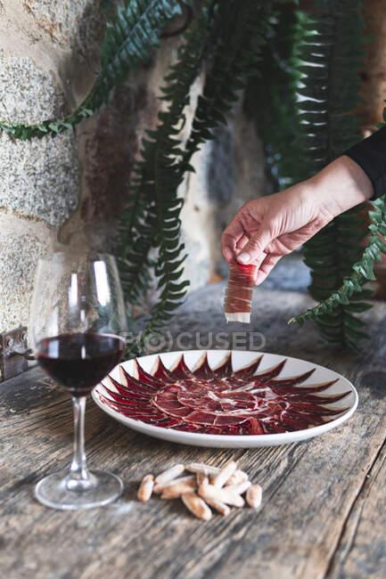 Chef arreglando rebanadas de carne en plato de vino en la mesa - foto de stock