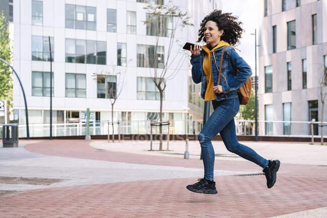 Mujer joven sonriente con mochila hablando por teléfono móvil mientras se ejecuta en la ciudad - foto de stock