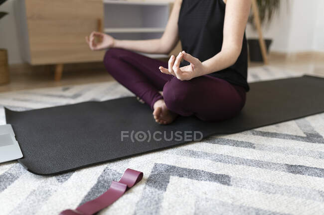 Женщина медитирует дома на коврике для упражнений — стоковое фото