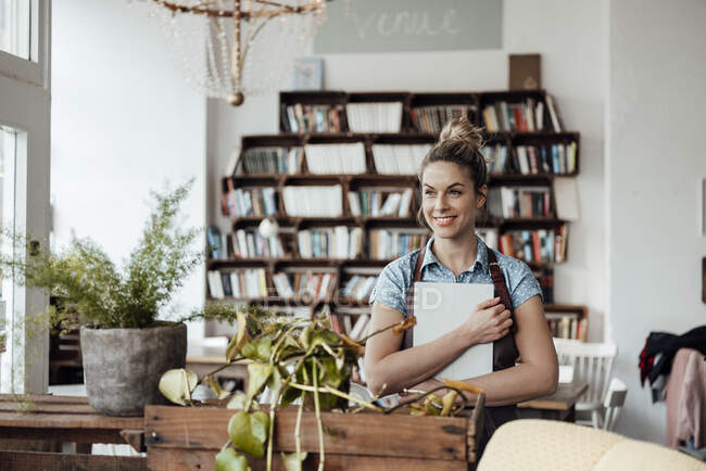 Улыбающаяся владелица держит цифровой планшет, стоя в кафе — стоковое фото