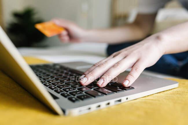 Женщина делает онлайн покупки через ноутбук, держа кредитную карту дома — стоковое фото
