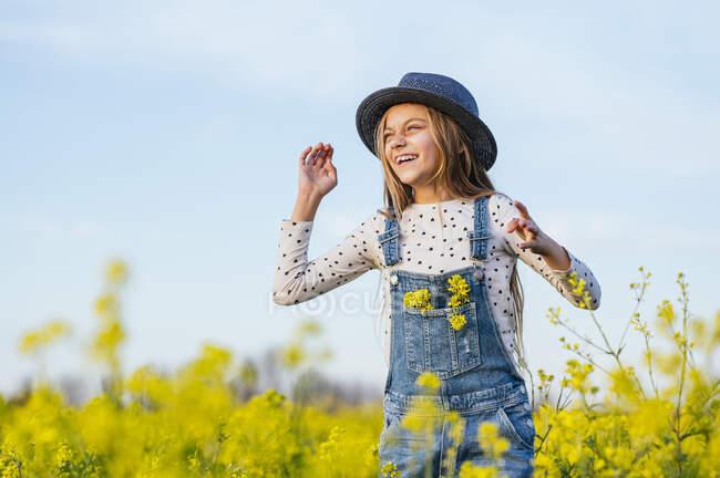 Chica alegre con sombrero de sol de pie en el campo agrícola - foto de stock