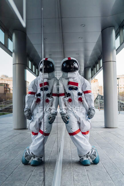 Male astronaut leaning on glass wall while standing on footpath - foto de stock