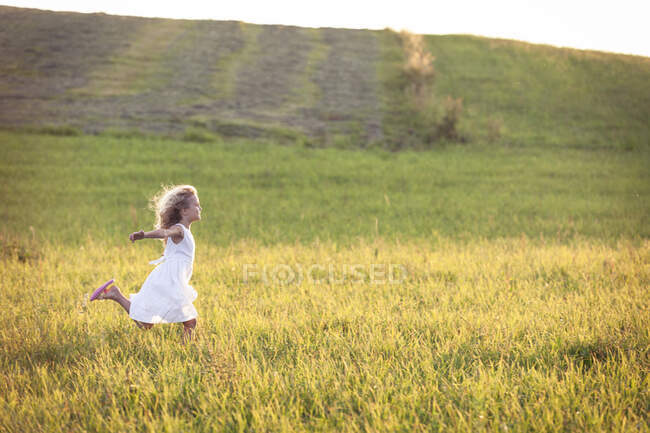 Девушка с вытянутыми руками бежит по лугу на закате — стоковое фото