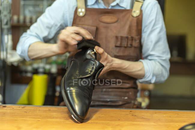 Couro macho segurando sapato durante o polimento na oficina — Fotografia de Stock