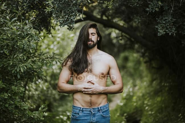 Homem sem camisa com os olhos fechados em pé e relaxante na floresta — Fotografia de Stock