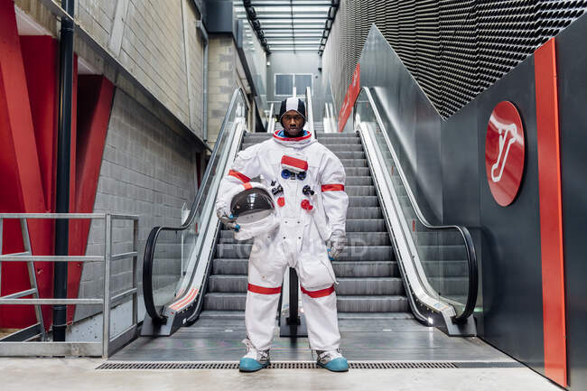 Mid adult man holding space helmet while standing in front of escalator - foto de stock