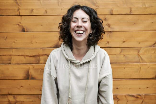 Donna felice in piedi vicino al muro di legno — Foto stock