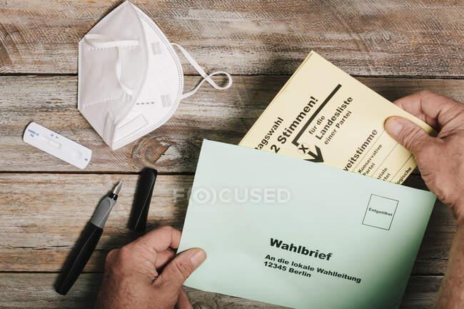 Mão colocando cédula para eleições federais em envelope na mesa com máscara protetora e teste rápido corona — Fotografia de Stock