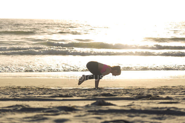 Jovem mulher balanceando na mão na praia no dia ensolarado — Fotografia de Stock