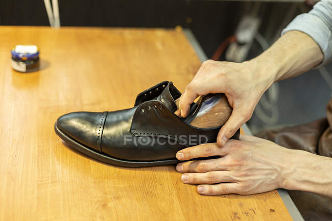 Macho artesão inserindo maca no sapato na oficina — Fotografia de Stock