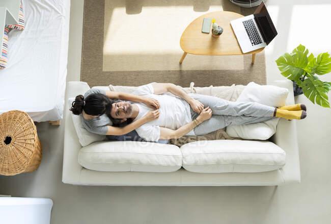 Hombre relajado acostado en el regazo de la mujer en la sala de estar en casa - foto de stock