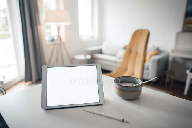 Tableta digital con comida en la mesa en casa - foto de stock