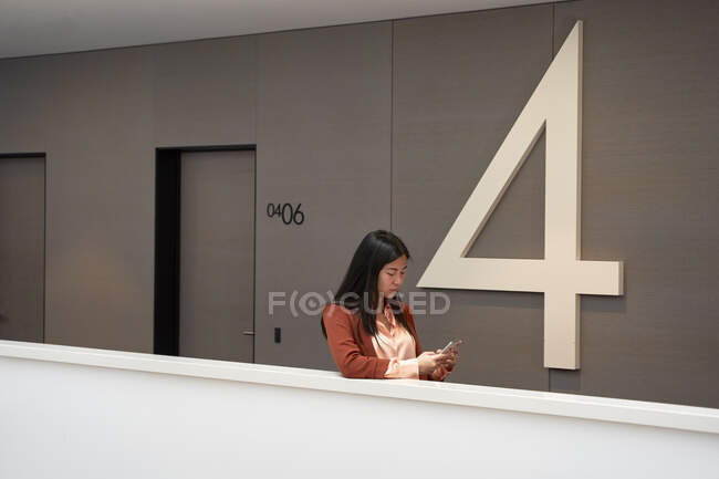 Joven empresaria usando teléfono inteligente reteniendo muro en corredor hotelero - foto de stock